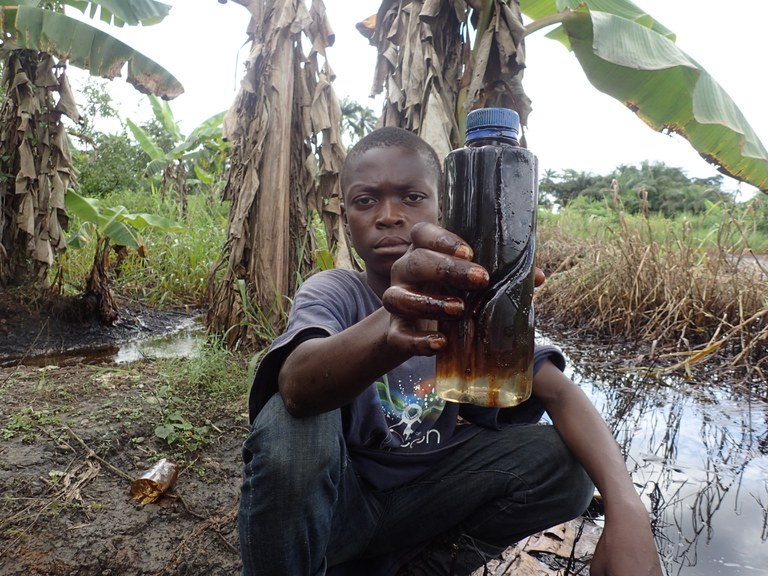 papilou met flesje olie achter zijn huis in ikarama - copyright Milieudefensie